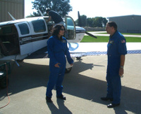 Greg (back to camera) performs pre-flight preparations as Tom warns me of the dangers of air sickness.